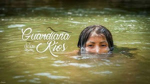 "[Image description: A young person with what black hair and brown skin submerged up to their nose in green river water. The person is smiling. The words ""Guardiana de los Rios"" are superimposed in white cursive text.]"